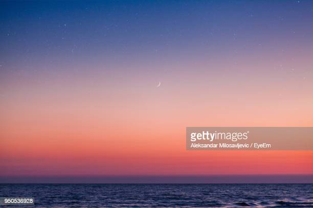 scenic view of sea against sky at night - avondschemering stockfoto's en -beelden