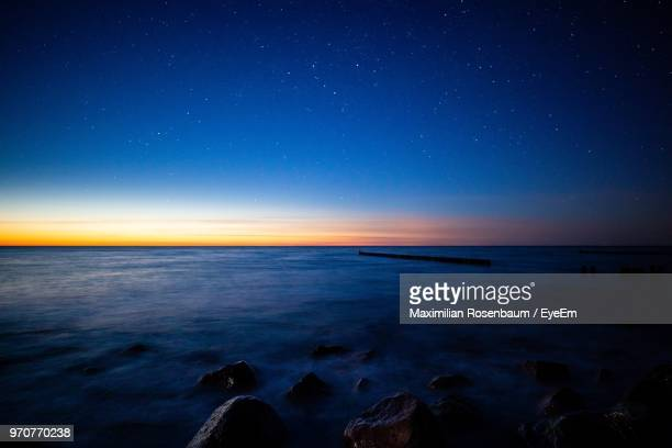 scenic view of sea against sky at night - horizon stock pictures, royalty-free photos & images
