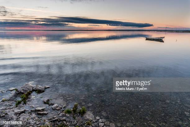 scenic view of sea against sky at sunset - muro stock photos and pictures