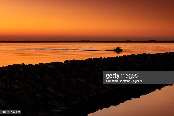 scenic view of sea against sky at sunset - christian soldatke stock pictures, royalty-free photos & images