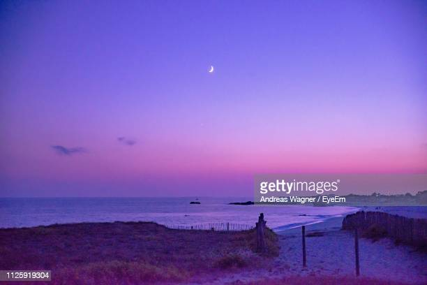 scenic view of sea against sky at sunset - purple sky stock pictures, royalty-free photos & images