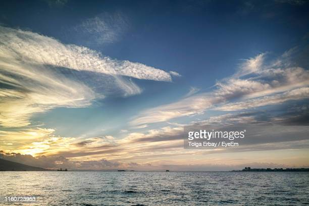 scenic view of sea against sky at sunset - tolga erbay stock photos and pictures