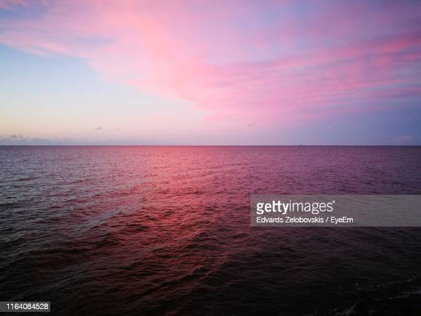 scenic view of sea against sky at sunset - pink sky stock pictures, royalty-free photos & images