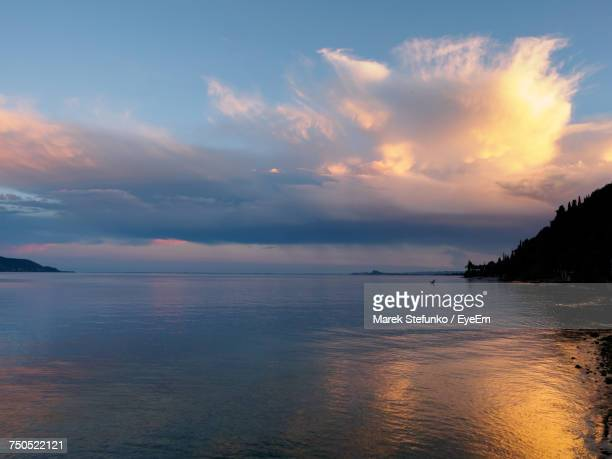 scenic view of sea against sky at sunset - marek stefunko stock photos and pictures
