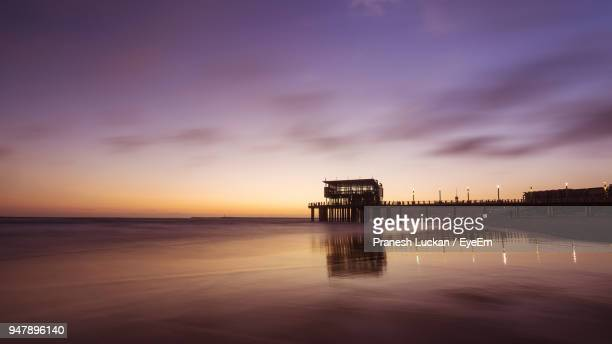 scenic view of sea against sky at sunset - durban beach stock photos and pictures