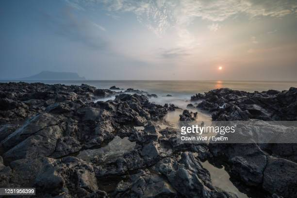 scenic view of sea against sky during sunrise - rocky coastline stock pictures, royalty-free photos & images