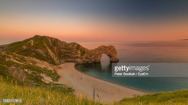 scenic view of sea against sky during sunset at durdle door in dorset - beach stock pictures, royalty-free photos & images