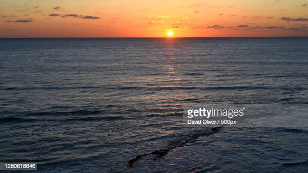 scenic view of sea against sky during sunset, compton bay, united kingdom - compton bay isle of wight stock pictures, royalty-free photos & images