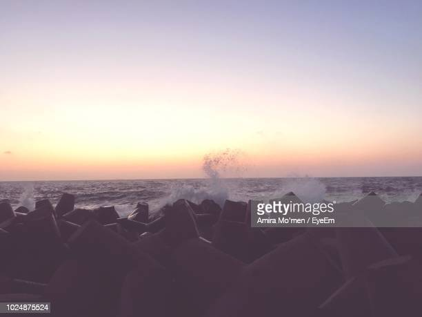 scenic view of sea against sky during sunset - men stockfoto's en -beelden
