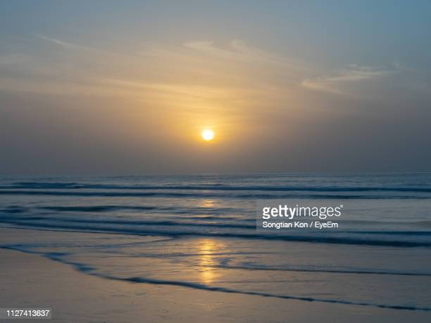 scenic view of sea against sky during sunset - gambia stock photos and pictures