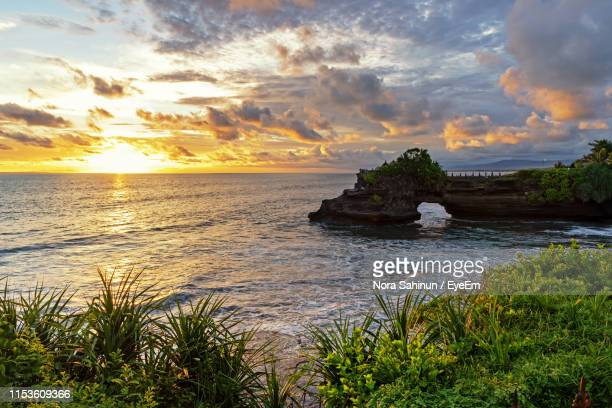 scenic view of sea against sky during sunset - tanah lot stock pictures, royalty-free photos & images