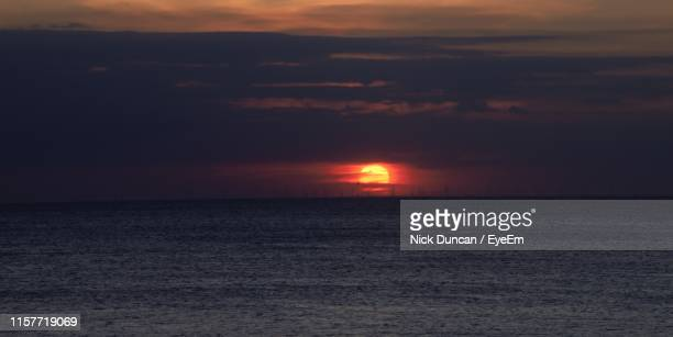 scenic view of sea against sky during sunset - blackpool beach stock pictures, royalty-free photos & images