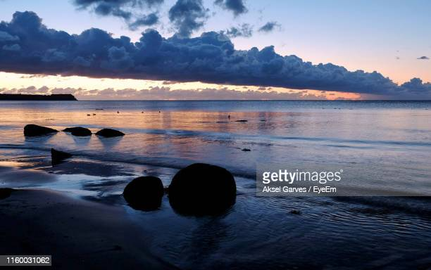 scenic view of sea against sky during sunset - aksel garves stock-fotos und bilder