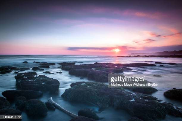 scenic view of sea against sky during sunset - made widhana stock photos and pictures