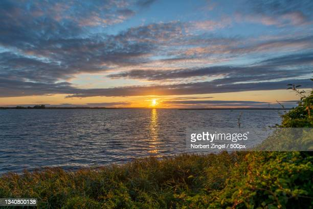 scenic view of sea against sky during sunset - norbert zingel stock-fotos und bilder