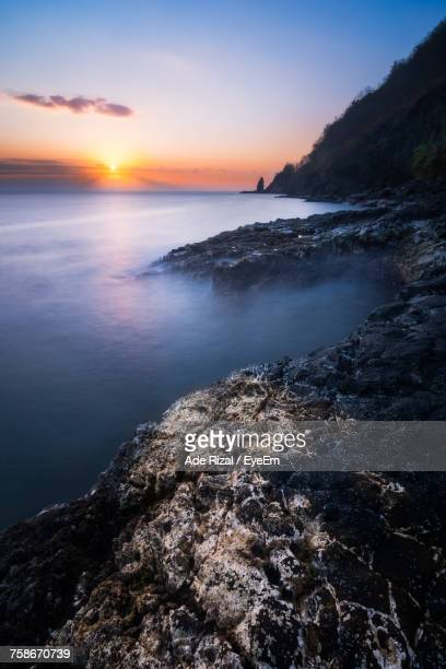 scenic view of sea against sky during sunset - ade rizal stock photos and pictures