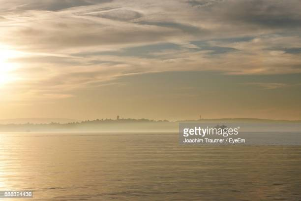 scenic view of sea against sky during sunset - bodensee stock-fotos und bilder