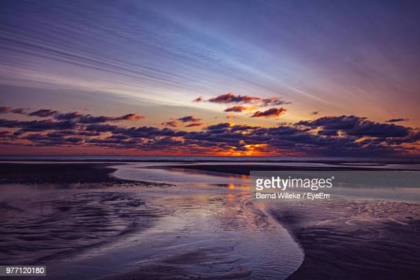 scenic view of sea against sky during sunset - sankt peter ording stock-fotos und bilder