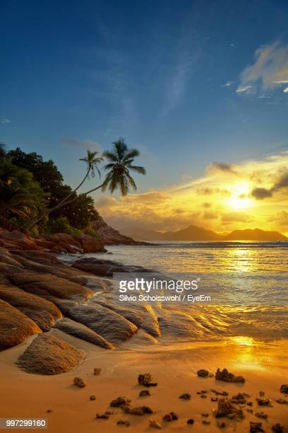 scenic view of sea against sky during sunset - la digue island stock pictures, royalty-free photos & images