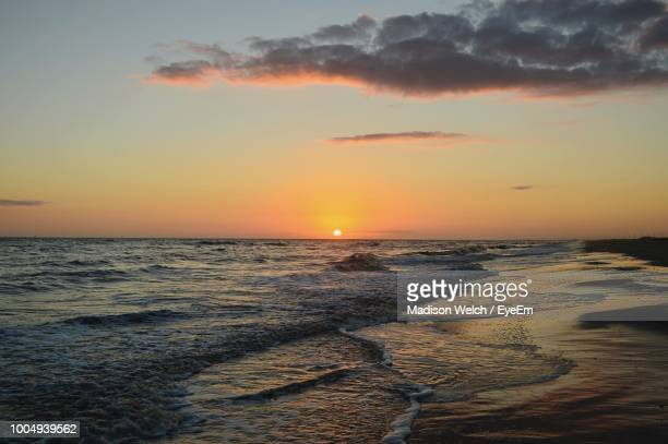 scenic view of sea against sky during sunsets - gulf shores alabama stock pictures, royalty-free photos & images