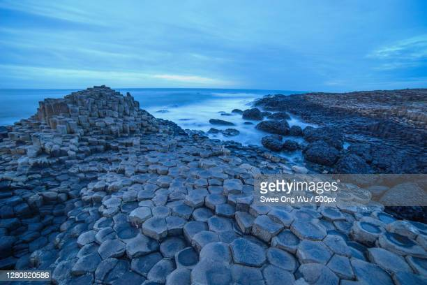 scenic view of sea against sky, giants causeway, bushmills bt sz, united kingdom - giant's causeway stock pictures, royalty-free photos & images