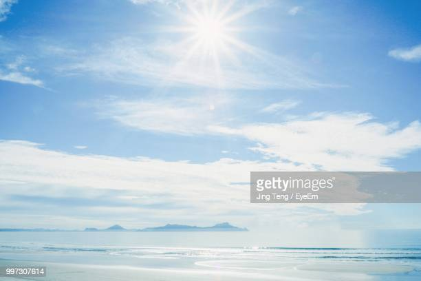 scenic view of sea against sky on sunny day - sonnig stock-fotos und bilder