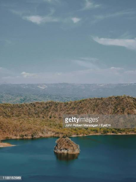 scenic view of sea against sky - taal volcano stock photos and pictures