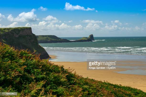 scenic view of sea against sky - gower peninsula stock photos and pictures
