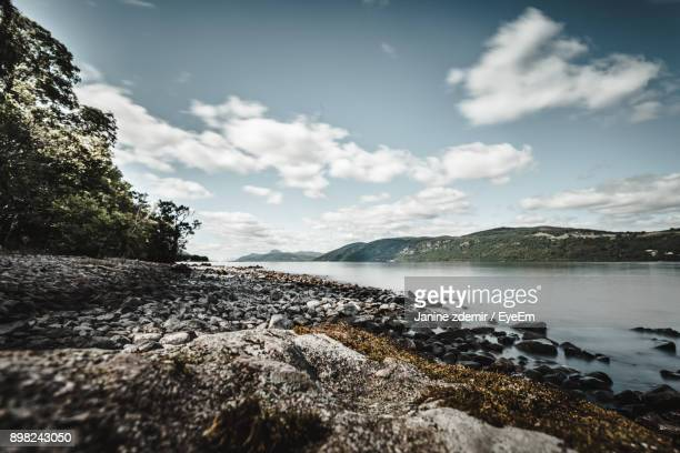 scenic view of sea against sky - loch ness stock photos and pictures