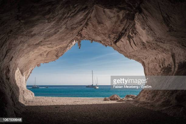 scenic view of sea against sky seen through cave - sardinia stock pictures, royalty-free photos & images