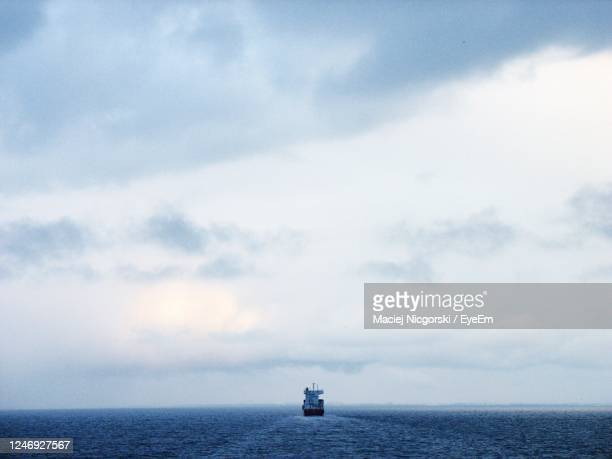 scenic view of sea against sky with a lonely ship - ferry stock pictures, royalty-free photos & images