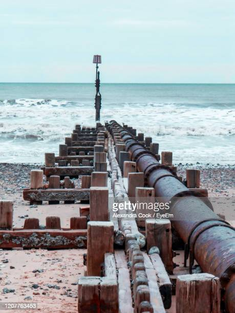 scenic view of sea against sky with groyne and pipe - tide stock pictures, royalty-free photos & images