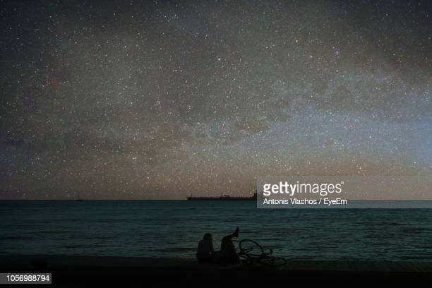 scenic view of sea against star field at night - 背景に人 ストックフォトと画像