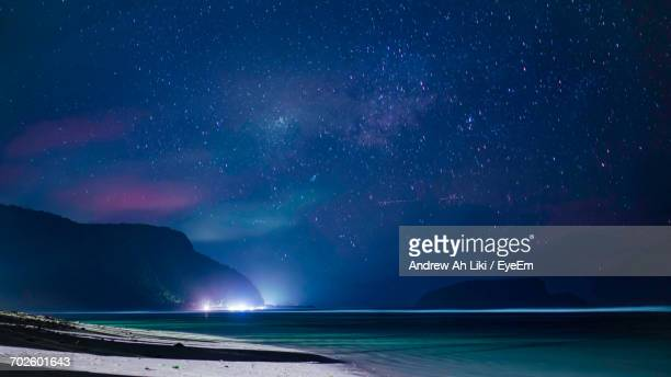 scenic view of sea against star field - apia stock photos and pictures