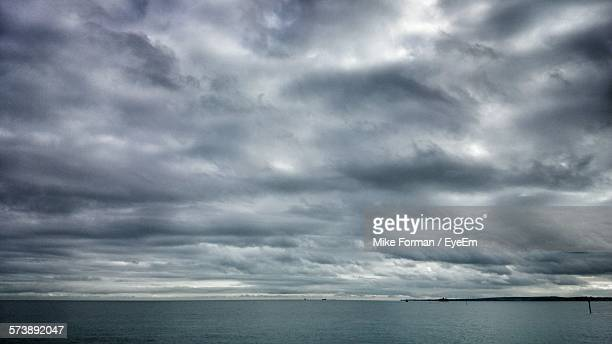 scenic view of sea against storm clouds - nube temporalesca foto e immagini stock