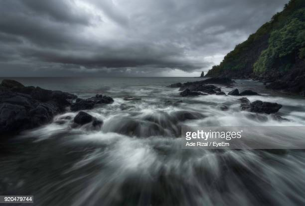 scenic view of sea against storm clouds - ade rizal stock photos and pictures