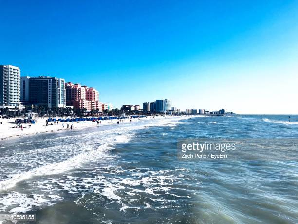 scenic view of sea and buildings against blue sky - クリアウォーター ストックフォトと画像