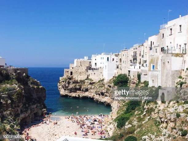 scenic view of sea and buildings against clear blue sky - polignano a mare stock photos and pictures