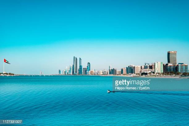 scenic view of sea and buildings against clear blue sky - abu dhabi stock pictures, royalty-free photos & images