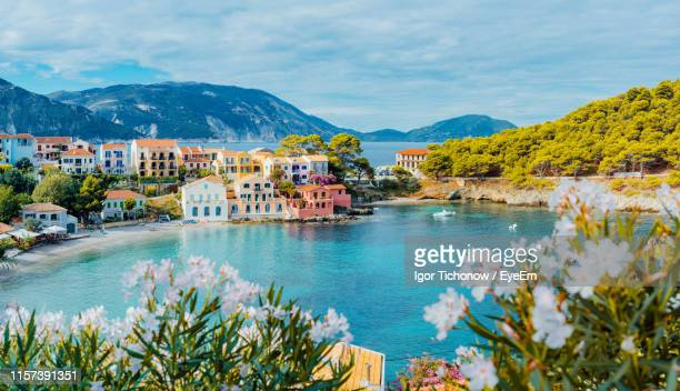 scenic view of sea and buildings against cloudy sky - greece stock pictures, royalty-free photos & images