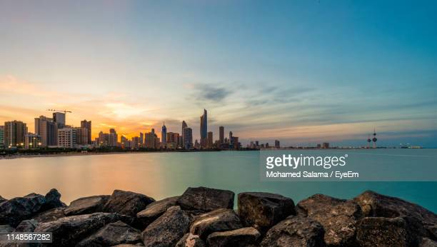 scenic view of sea and buildings against sky during sunset - kuwait stock pictures, royalty-free photos & images