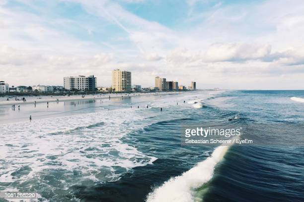 scenic view of sea and buildings against sky - jacksonville beach stock pictures, royalty-free photos & images