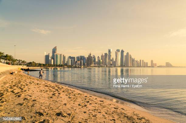scenic view of sea and buildings against sky - doha photos et images de collection