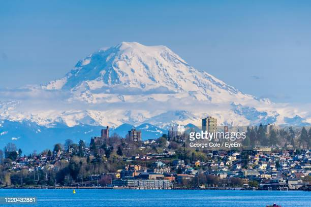 scenic view of sea and buildings against sky - washington state stock pictures, royalty-free photos & images