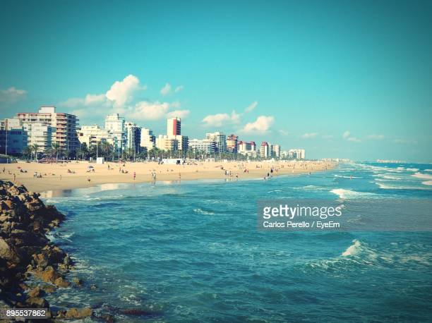 Scenic View Of Sea And Cityscape Against Blue Sky