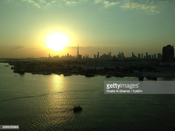 Scenic View Of Sea And Cityscape Against Sky During Sunset