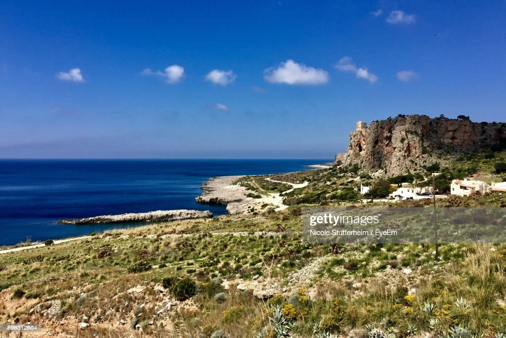 Scenic View Of Sea And Cliff Against Blue Sky : Stock Photo