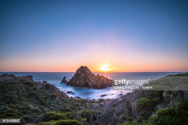 Scenic View Of Sea And Cliff Against Sky During Sunset