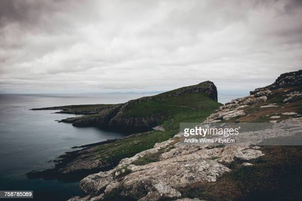 scenic view of sea and cliff against sky - andre wilms eyeem stock-fotos und bilder