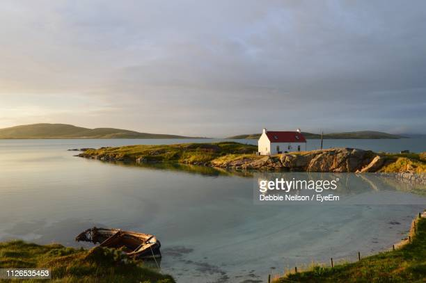 scenic view of sea and houses against sky - barra scotland stock pictures, royalty-free photos & images
